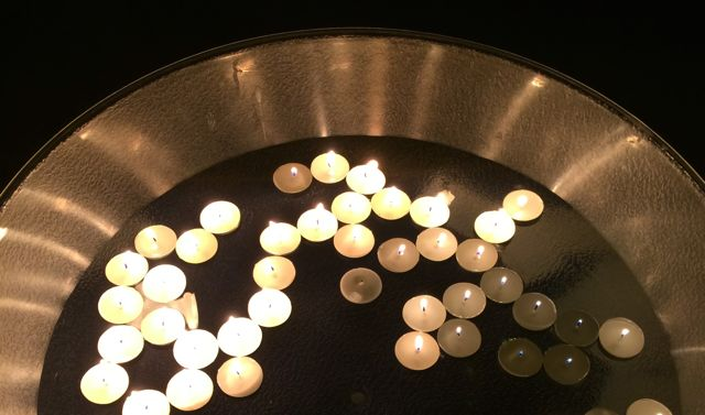 Thirty tea lights in a bowl of water at a winter ceremony.