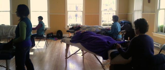 Current students practicing craniosacral therapy. Some students are lying on massage tables and some are touching in at the feet.